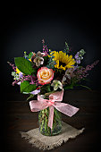 A close up vertical photograph of a pretty arrangement of colorful flowers in a glass vase with a dainty pink ribbon around it. The flowers are isolated on black with  copy space on top.
