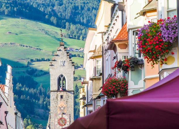 colorful flowers in vipiteno, splendid town in the italian alps, with the beautiful medieval gate of the old town stock photo