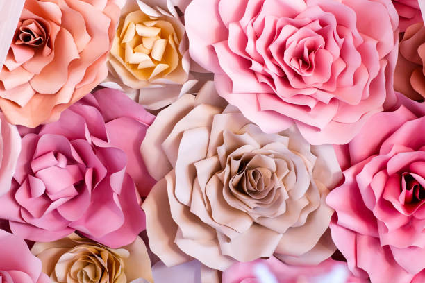 Colorful flowers paper background. Red, pink, purple, brown, yellow and peach handmade paper roses stock photo