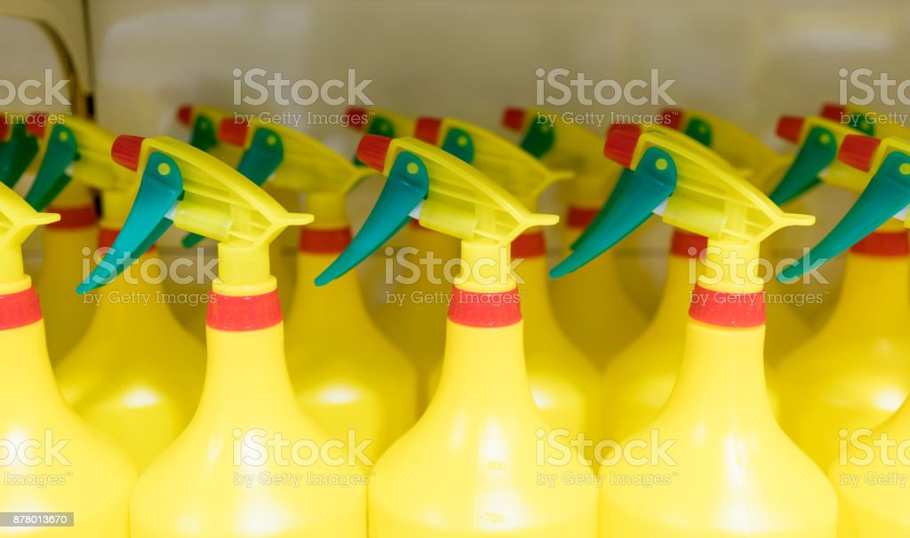 Colorful foggy spray plastic bottles with red nozzle and green handle arranged on shelf. Equipment for multipurpose cleaning. stock photo