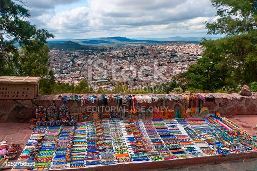 Zacatecas, Mexico - October 25, 2006: Colorful folk art made by indigenous Huichol Indians, atop Cerro De La Buffa mountain, with a view of the city below.
