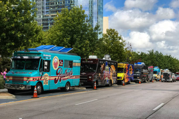 Colorful Food Trucks Parked In A Row On Dallas Street Dallas, TX, USA - October 6, 2018:  Several colorful food trucks are parked all in a row on a street beside a public park on a Saturday on October 6, 2018 in Dallas, TX. food truck stock pictures, royalty-free photos & images