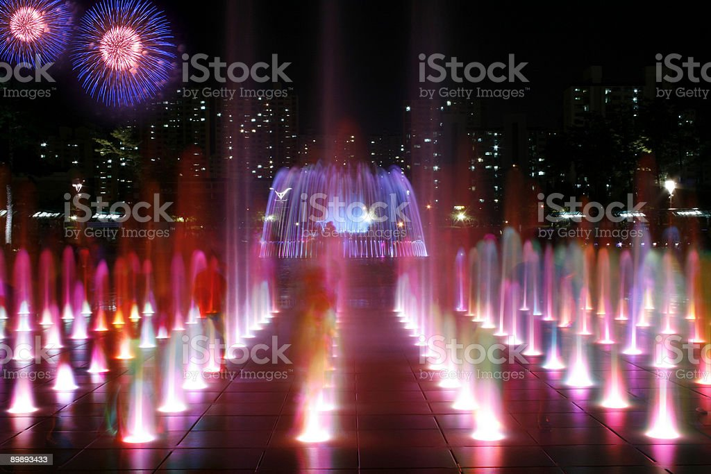 Colorful Fountain At Night and Fireworks stock photo
