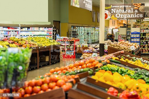 Colorful fresh fruits and vegetables are displayed in produce section of local grocery store or supermarket. Rows of tomatoes, peppers, potatoes, bananas, apples, and other natural organic produce is arranged on shelves and tables.