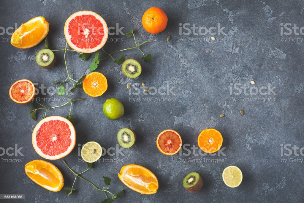 Colorful fresh fruit on dark background. Flat lay, top view royalty-free stock photo