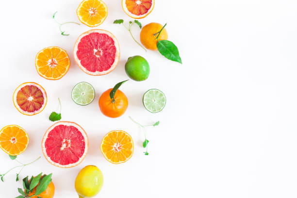 colorful fresh fruits on white table. flat lay, top view - agrume foto e immagini stock