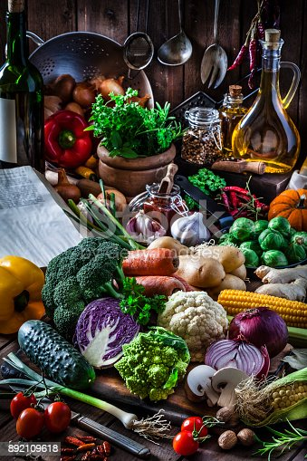 Vertical shot of fresh organic vegetables on rustic kitchen table. The composition includes lettuce, bell peppers, tomatoes, edible mushrooms, cauliflower, cucumber, broccoli, onion, carrot, corn, and chili peppers. An old cookbook is partially visible at the left. Low key DSRL studio photo taken with Canon EOS 5D Mk II and Canon EF 100mm f/2.8L Macro IS USM
