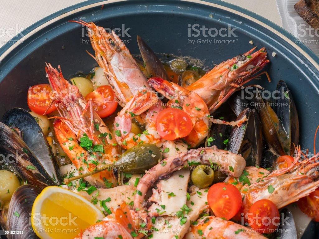 Colorful fresh seafood with vegetables and spices on blue plate in restaurant stock photo