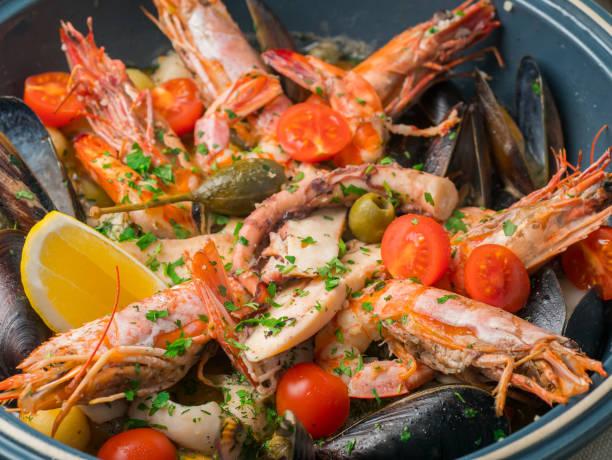 bunte frische meeresfrüchte mit gemüse und gewürzen auf blaue platte im restaurant - meeresfrüchte enchiladas stock-fotos und bilder