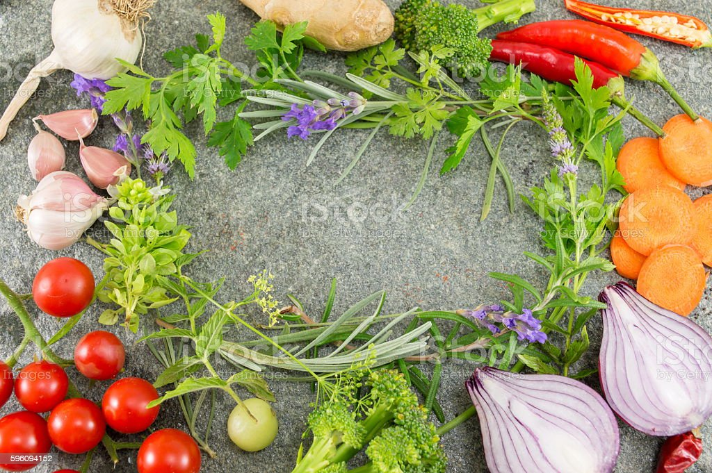 Colorful fresh vegetables and herbs scattered on table royalty-free stock photo