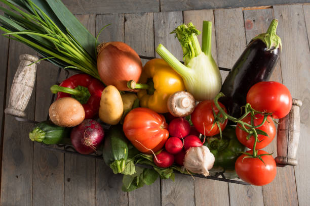 Colorful fresh vegetables in a basket Colorful fresh vegetables in a basket on a old shabby wooden table vielfalt stock pictures, royalty-free photos & images