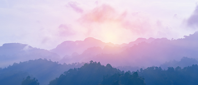 Sunrise from the edge of foggy mountain after raining in the night. The colors of sky and mountains change to purple and blue.