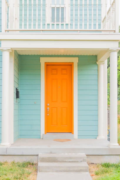 Colorful front facade or porch Freshly painted home with tangerine door and baby blue siding front door stock pictures, royalty-free photos & images