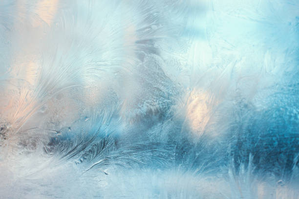 colorful frosty pattern on the window - ghiacciato foto e immagini stock