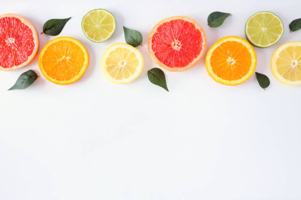 Colorful fruit border of citrus slices and leaves, top view over a white background stock photo