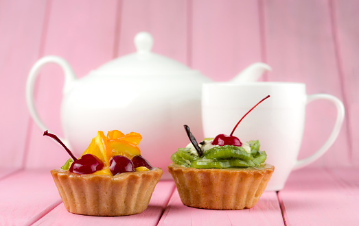 Colorful fruit cakes made with kiwi, orange, candied cherries and chocolate on a pink background with a teapot and cup