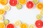 Colorful fruit frame of fresh citrus slices. Top view, flat lay over a white background with copy space.