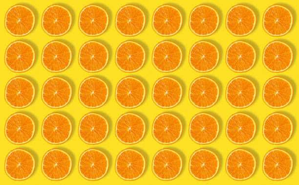 colorful fruit pattern of fresh orange slices on yellow background. from top view - orange fruit stock photos and pictures