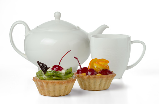 Colorful fruitcakes made with kiwi, orange, candied cherry, cream and chocolate isolated on a white background with a cup and a teapot