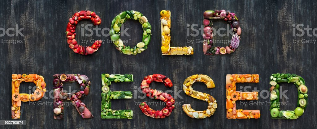Colorful fruits and vegetables laid out to form the word cold pressed stock photo