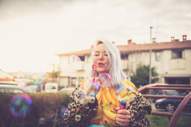シャボン玉を吹くカラフルなファンキーな女性 - showus ストックフォトと画像