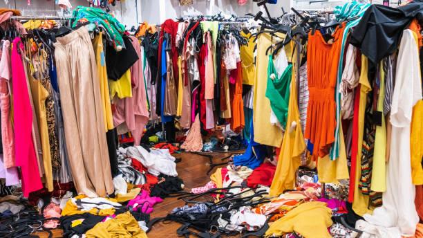 raflarda ve zeminde renkli giysiler; hızlı moda konsepti - buruşuk fiziksel özellikler stok fotoğraflar ve resimler