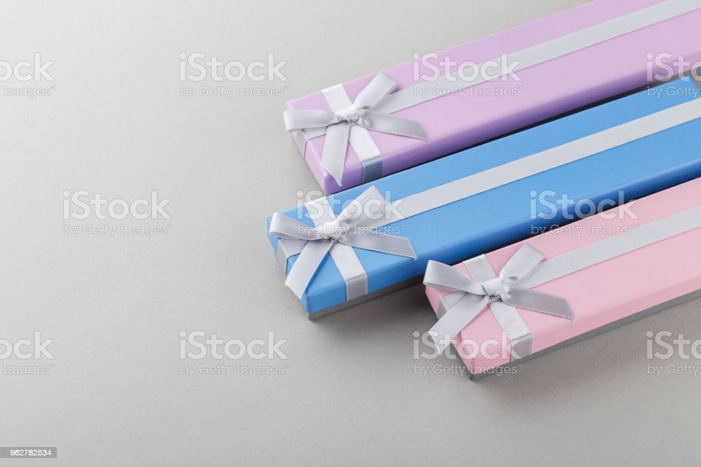 colorful gift boxes with ribbon bows on gray background - Foto stock royalty-free di Anniversario