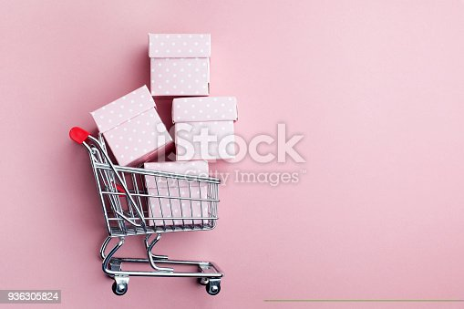 istock Colorful gifts box, supermarket shopping cart on pink background 936305824