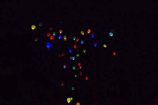 Colorful, glowing Balloons Flying in the Dark Night Sky