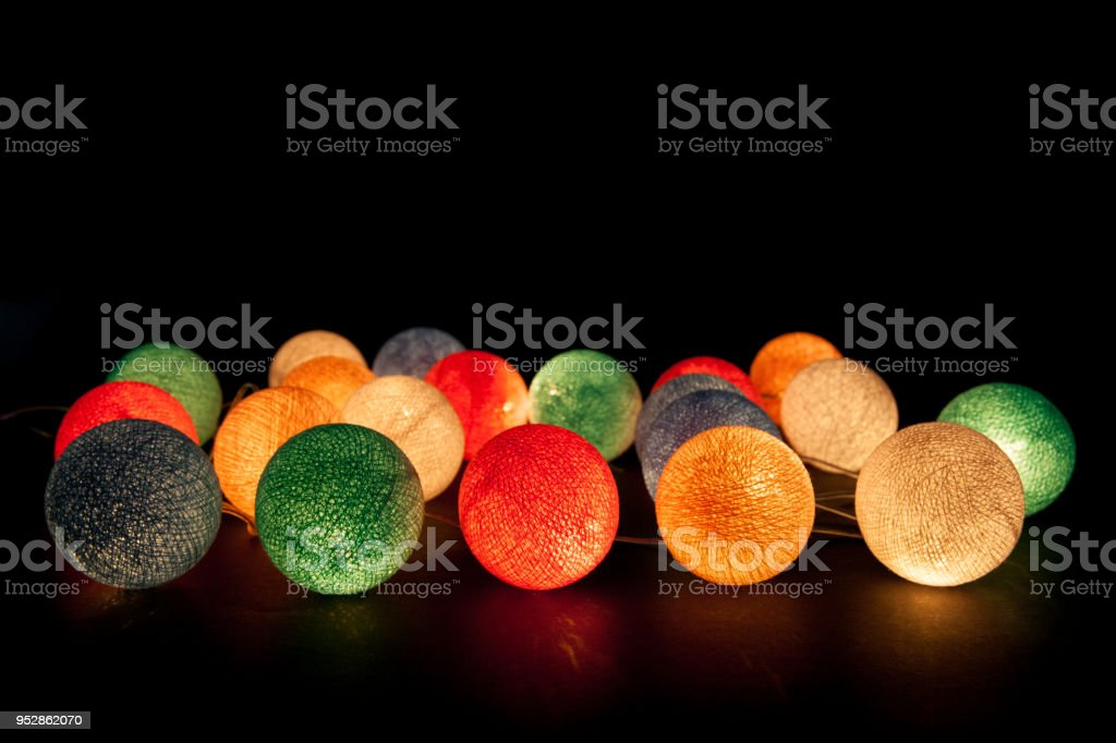 Colorful glowing balls on a black background. Glowing garland at night. Colorful circles on the background. – zdjęcie