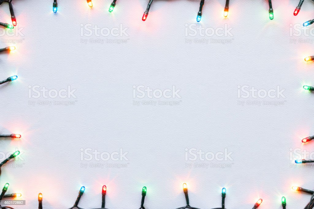 colorful glowing garland on white background Christmas frame mockup stock photo