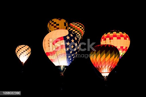 A group of glowing hot air balloons in the night sky