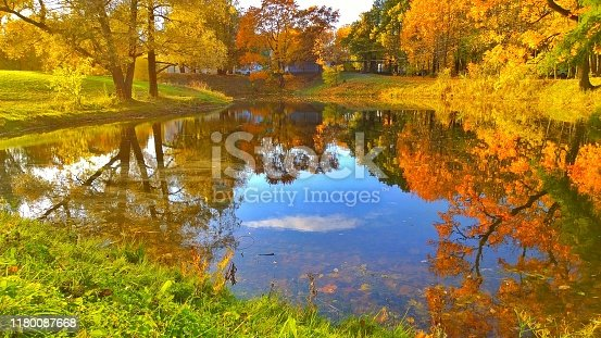 Colorful Golden autumn in the park. Reflection of blue sky and green, yellow and orange trees and in a pond. Fall Scene. Ecology concept. Beautiful season landscape. Travel destination