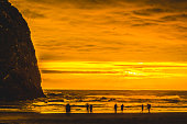 Colorful Golden Sunset Seabirds Haystack Rock Sea Stack Canon Beach Clatsap County Oregon.  Originally discovered by Clark of Lewis Clark in 1805