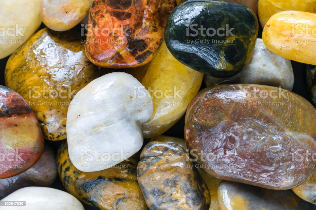 Colorful granite river rocks with water droplets stock photo