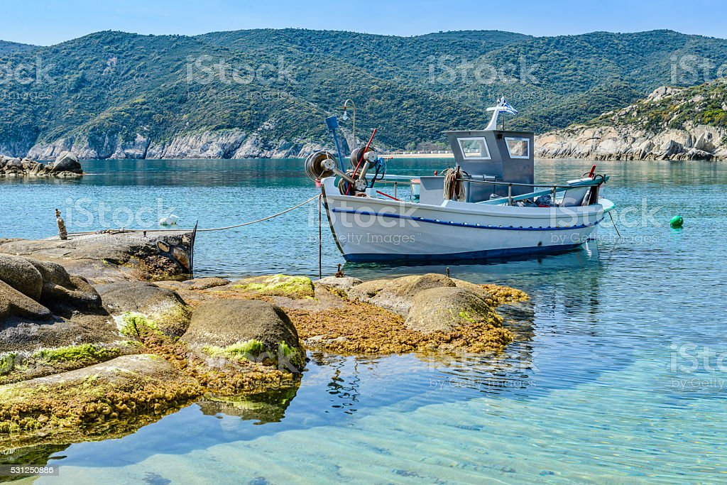Colorful Greek fishing boat in the natural bay stock photo