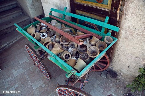 colorful green wooden old cart with clay pot