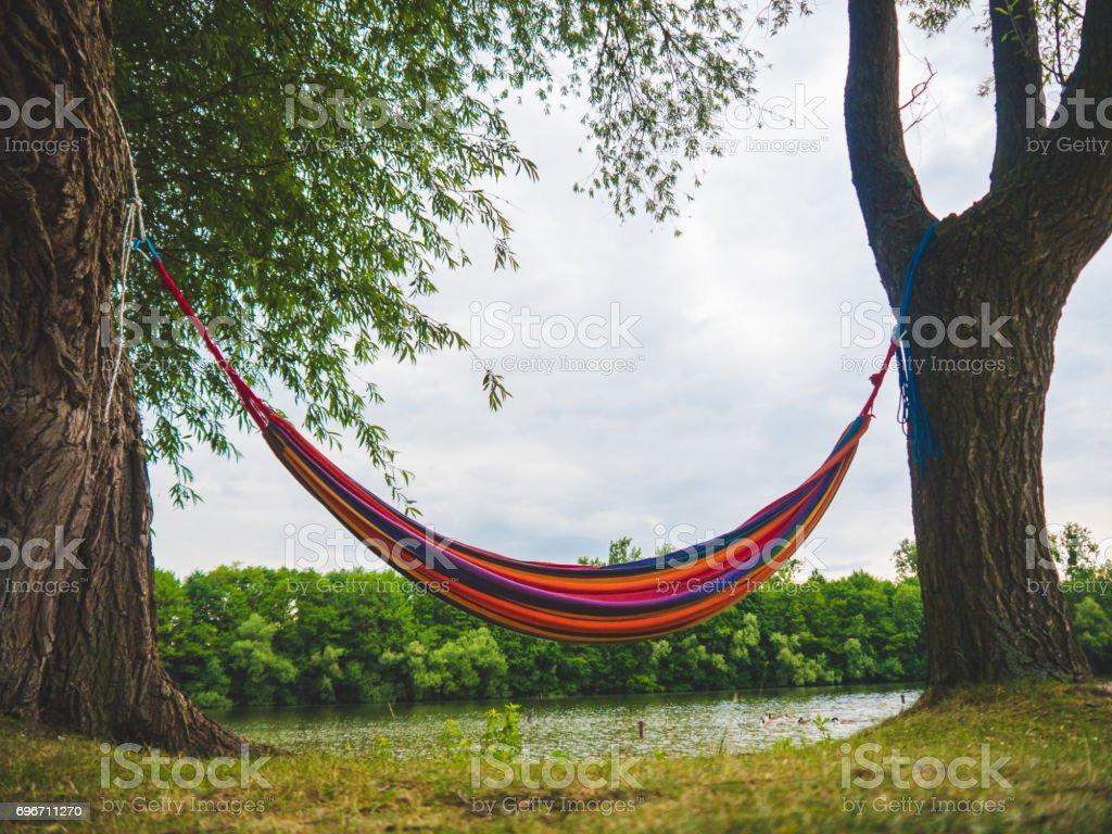 Bunte Hängematte zwischen zwei Bäumen an einem See – Foto