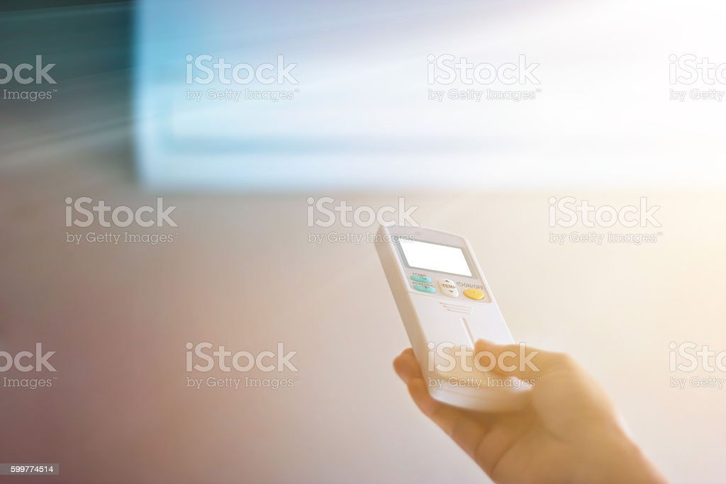Colorful, hand with remote control to the airconditioner stock photo