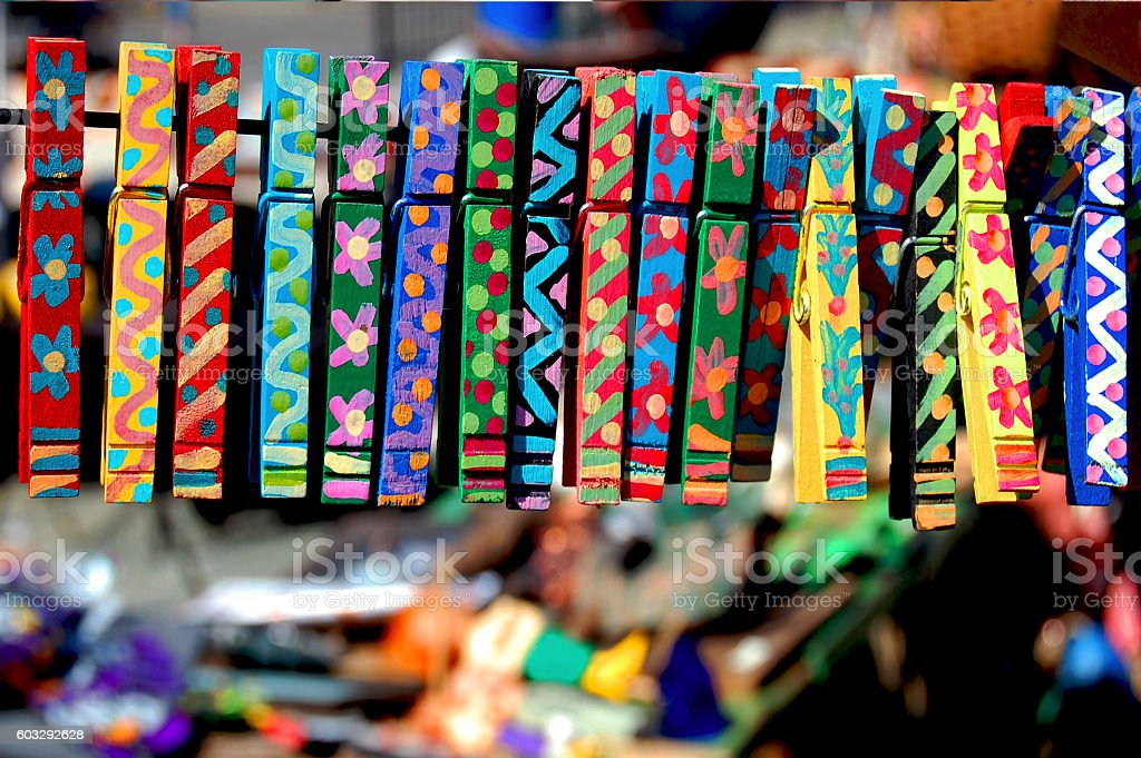 Colorful hand-painted clothes pins displayed at a craft show. stock photo