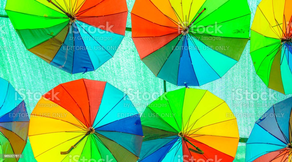 Colorful hanging umbrellas above the street on green sheet royalty-free stock photo