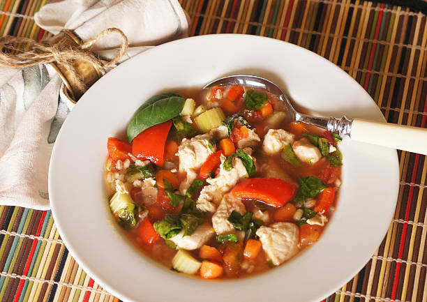 Colorful Healthy Soup! Colorful, healthy soup with chicken, carrots, celery, spinach, red bell peppers, basil, and tomatoes... yum! vegetable soup stock pictures, royalty-free photos & images