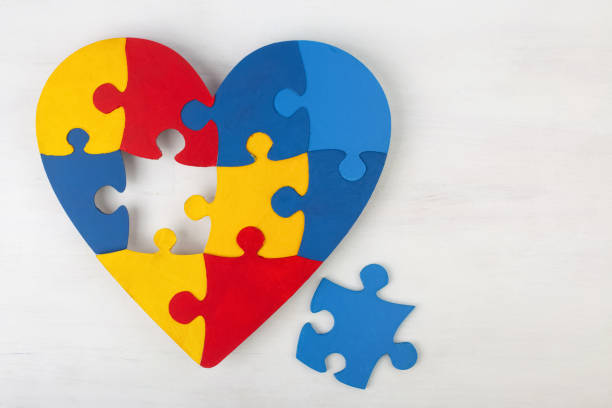 A colorful heart made of symbolic autism puzzle pieces. stock photo