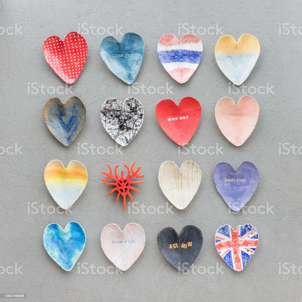 Colorful Heart Shape Plates Decoration On Cement Wall Background