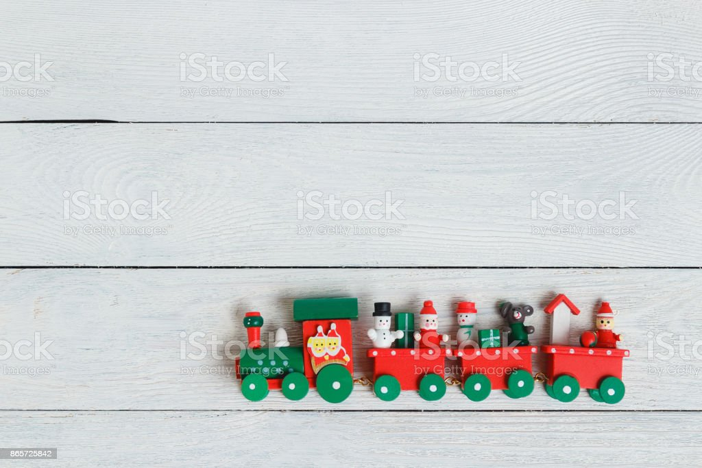 A colorful holiday Christmas train over a white wooden background....