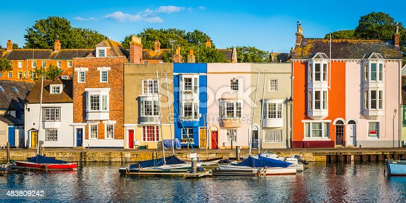 istock Colorful homes quaint cottages in sunny fishing village harbor panorama 483809242