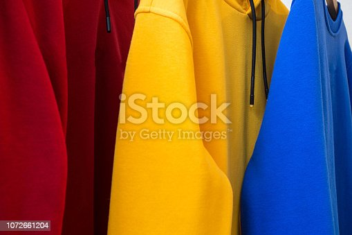 Colorful hoodies on hangers close-up modern design fabric texture