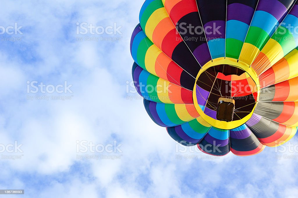 Colorful hot air balloon against blue cloudy sky stock photo