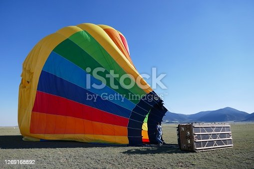 Colorful hot air balloon deflating on ground after flight