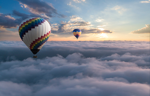 Colorful hot air balloon flying above the clouds